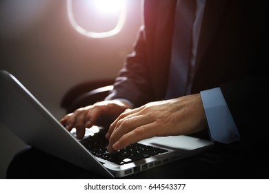 mature businessman working with notebook while sitting inside an airplane