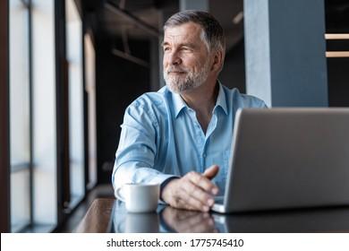 Reifender Geschäftsmann, der auf Laptop arbeitet. Schöner reifer Geschäftsführer in einem modernen Büro