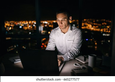 Mature businessman working on a laptop at his office desk late in the evening in front of windows overlooking the city