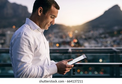 Mature businessman working online with a digital tablet while standing outside on an office building balcony overlooking the city at dusk