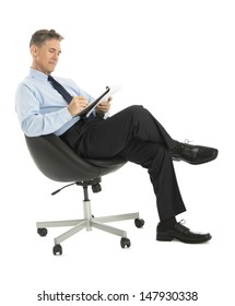 Mature businessman writing in note pad while sitting on office chair against white background