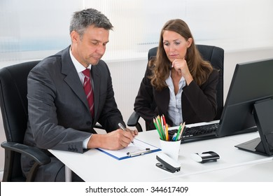 Mature Businessman Writing On Clipboard With Female Assistant At Desk In Office