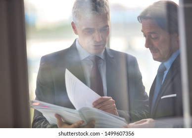 Mature businessmen discussing over document seen through glass in new office