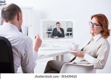 Mature businesspeople sitting beside desk in light office, talking with young businessman via video chat