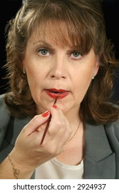 Mature businesswoman applies lip gloss looking at camera.