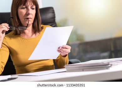 Mature businesswoman checking document in office, light effect