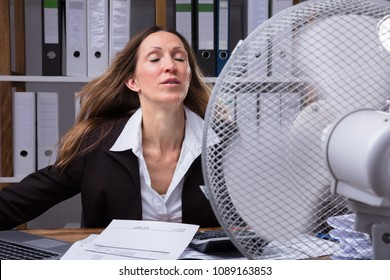 Mature Businesswoman Cooling Herself In Front Of Fan During Hot Weather