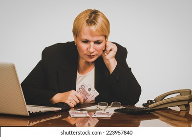Mature businesswoman counting the money.