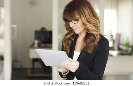 Mature Businesswoman with Digital Tablet in Office