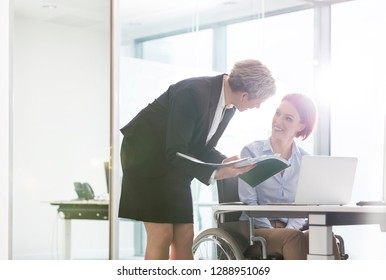 Mature businesswoman discussing over document with disabled colleague at desk in office with lens flare in background