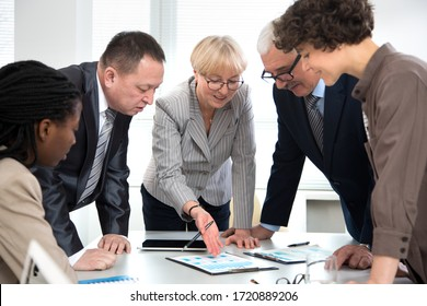 Mature businesswoman explains to colleagues a new project in the modern office