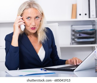 Mature businesswoman having phone call conversation at workplace in office