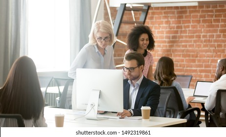 Mature businesswoman mentor helping employee with corporate software, training staff, using computer, team leader giving instructions to subordinate, diverse colleagues working in shared workspace