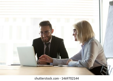Mature businesswoman mentor helping new employee with corporate software, using laptop, colleagues working on project together, friendly senior manager consulting client about loan or insurance
