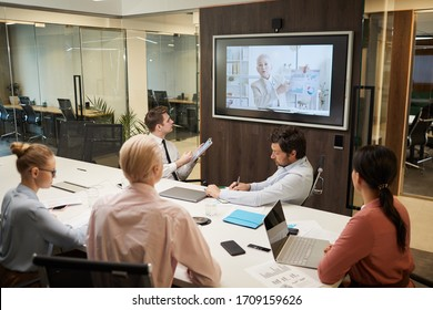 Mature businesswoman o the screen holding the online conference for business people who sitting at the table and listening to her at office