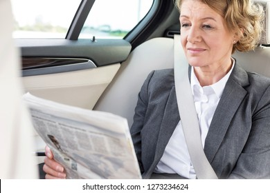 Mature businesswoman reading newspaper while sitting in car