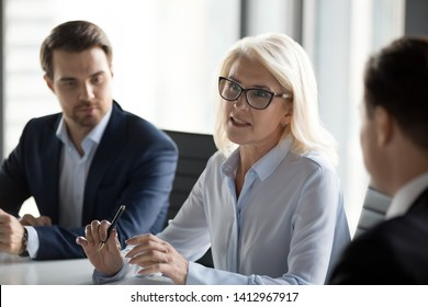 Mature businesswoman speak during company business meeting in office, serious elderly female team leader talk holding corporate briefing, negotiating with partners. Collaboration concept