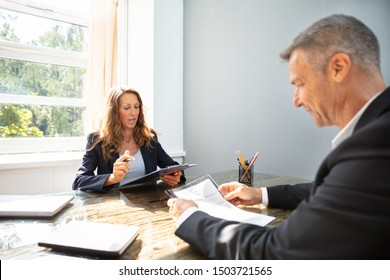 Mature Businesswoman Taking An Interview Of Man Over The Wooden Desk In Office