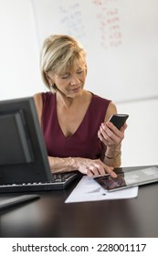 Mature businesswoman using technologies at desk in office