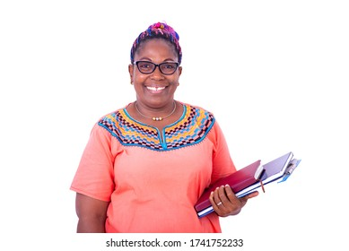 mature businesswoman wearing glasses, standing with notebooks in hand while smiling at camera.