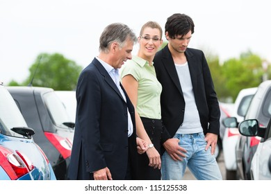 Mature car dealer and young couple standing on parking place at dealership in front of cars