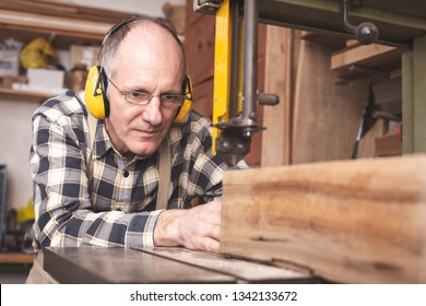 Mature carpenter deeply focused on cutting a piece of wood with a band saw