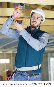 mature carpenter drilling wood