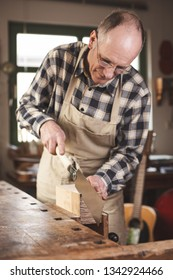 Mature carpenter using a double edged Japanese pull saw inside his workshop
