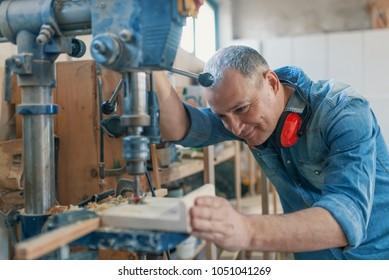 Mature carpenter using drill press in workshop. Wood working. Carpentry workshop routine. Engineer in workshop