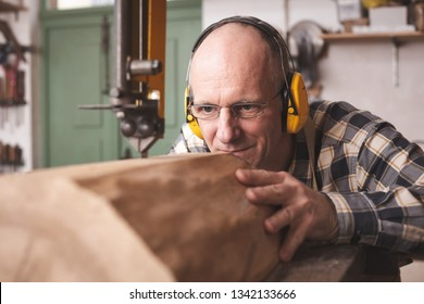 Mature carpenter in a workshop cutting a piece of wood with a band saw