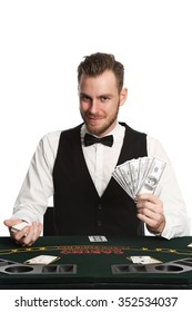 Mature casino worker wearing a black vest and white shirt with a bowtie. Holding a fan of dollar bills with a deck of cards spread in front of him. White background.