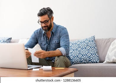 Mature casual man using laptop while looking at invoice. Smiling latin man managing finance with bills and laptop while sitting on couch at home. Hispanic guy reading expenses wearing eyeglasses.
