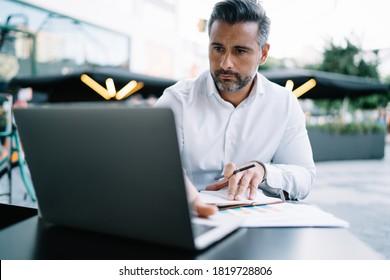 Reifender kaukasischer Geschäftsführer analysiert Webinformationen während der Organisationsplanung in Straßencafeteria, Geschäftsmann mittleren Alters, der Nachrichten über Netbook-Technologie mit 4g drahtloser 4g-Technik liest