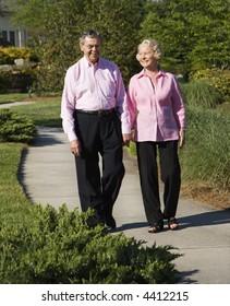 Mature Caucasian couple walking down sidewalk.