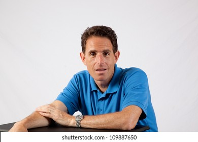 Mature Caucasian male sitting with his forearms on a table, and a friendly smile for the camera