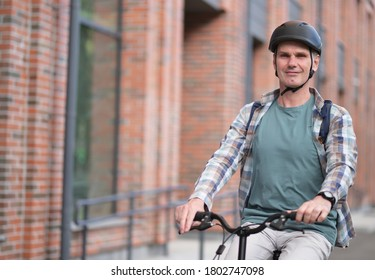 Mature Caucasian man in a bicycle helmet on his bike in a city