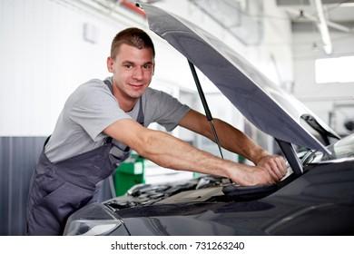 A mature caucasian man checking an oil level under car engine hood.