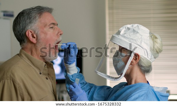 A mature Caucasian man in a clinical setting being swabbed by a healthcare worker in protective garb to determine if he has contracted the coronavirus or COVID-19.