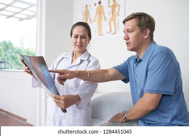 Mature Caucasian man discussing his chest x-ray with doctor