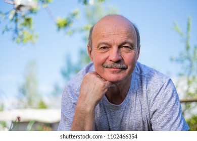A mature caucasian man resting outdoor on sunny summer day. He is smiling. Close up portrait of face