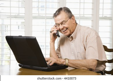 Mature Caucasian man typing on laptop and talking on cellphone.