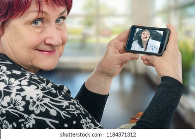 Mature caucasian woman enjoys telecommunication with virtual doctor. She holds her mobile phone in two hands the physician talks to her on the screen showing some diagrams.