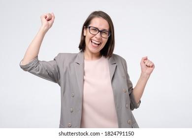 Mature caucasian woman in glasses doing a winner gesture raising fists up. Studio shot