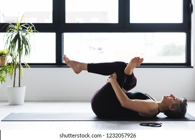 Mature Caucasian woman practicing yoga on living room floor. Middle aged woman doing yoga indoors.