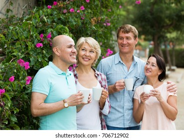 Mature cheerful males and females drinking coffee outdoors