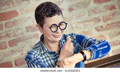 Mature cheerful woman checking the time lokking at her wrist watch
