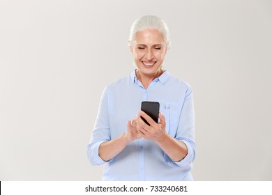 Mature concentrtated grey-haired woman using smartphone and smiling isolated over white