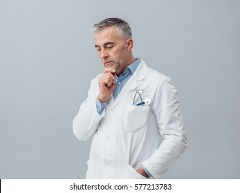 Mature confident doctor thinking and taking decisions with hand on chin