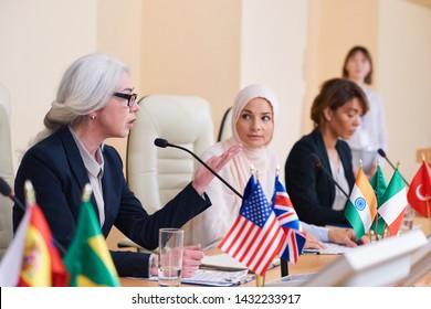 Mature confident female speaker in elegant suit explaining her opinion