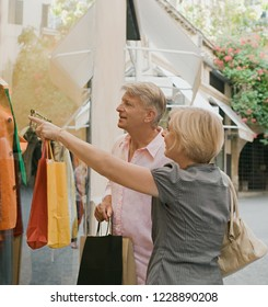 Mature consumer couple visiting city on holiday shopping in picturesque street, outdoors. Senior man and woman together looking at store window carrying bags, recreation leisure lifestyle.